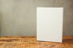 Άσπρος καμβάς στον ξύλινο πίνακα πέρα από το αγροτικό υπόβαθρο Χλεύη επάνω στο πρότυπο στοκ εικόνα