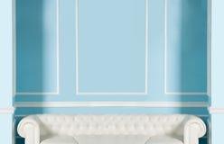Άσπρος καναπές σε ένα υπόβαθρο του μπλε τοίχου Στοκ φωτογραφία με δικαίωμα ελεύθερης χρήσης