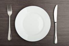 Άσπρος κενός μαχαιριών δικράνων πιάτων Στοκ εικόνα με δικαίωμα ελεύθερης χρήσης