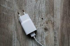 Άσπρος κινητός τηλεφωνικός φορτιστής στο ξύλινο υπόβαθρο Προσροφητικός άνθρακας Smartphone στοκ εικόνες