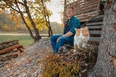 Άσπρος-κόκκινη γάτα στο πρώτο πλάνο και θολωμένο άτομο στο υπόβαθρο στοκ φωτογραφίες
