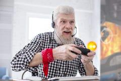 Άσπρος-μαλλιαρό ανώτερο άτομο που διεγείρεται για το παιχνίδι του τηλεοπτικού παιχνιδιού στοκ φωτογραφία με δικαίωμα ελεύθερης χρήσης