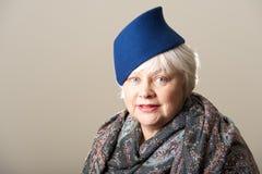 Άσπρος-μαλλιαρή γυναίκα στο μπλε καπέλο και το μαντίλι Στοκ Εικόνα