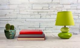 Άσπρος ξύλινος πίνακας με τα βιβλία, έναν λαμπτήρα και έναν κάκτο στοκ εικόνες