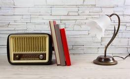 Άσπρος ξύλινος πίνακας με τα βιβλία ένας λαμπτήρας και ένα εκλεκτής ποιότητας ραδιόφωνο στοκ εικόνες με δικαίωμα ελεύθερης χρήσης