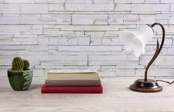 Άσπρος ξύλινος πίνακας με τα βιβλία ένας λαμπτήρας και ένας κάκτος στοκ φωτογραφίες με δικαίωμα ελεύθερης χρήσης