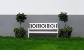 Άσπρος ξύλινος πάγκος στον κήπο Στοκ Φωτογραφίες