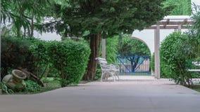 Άσπρος πάγκος σε ένα θερινό πάρκο που περιβάλλεται από τους πράσινους Μπους και τις εγκαταστάσεις στοκ φωτογραφίες με δικαίωμα ελεύθερης χρήσης