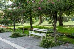 Άσπρος πάγκος σε ένα όμορφο πράσινο πάρκο Στοκ φωτογραφία με δικαίωμα ελεύθερης χρήσης