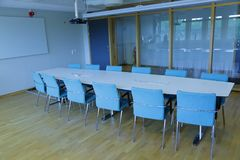 Άσπρος πίνακας γραφείων με δώδεκα καρέκλες στην αίθουσα συνεδριάσεων Στοκ Φωτογραφία