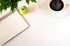 Άσπρος πίνακας γραφείων γραφείων σχεδιαστών με την κενή σελίδα σημειωματάριων με το φλιτζάνι του καφέ και το μήλο Η τοπ άποψη, επ Στοκ εικόνα με δικαίωμα ελεύθερης χρήσης