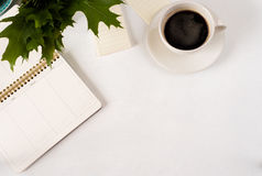 Άσπρος πίνακας γραφείων γραφείων σχεδιαστών με την κενή σελίδα σημειωματάριων με το φλιτζάνι του καφέ Η τοπ άποψη, επίπεδη βάζει Στοκ Φωτογραφίες