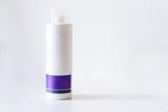 Άσπρος πορφυρός πλαστικός σωλήνας κρέμας ομορφιάς μπουκαλιών καλλυντικών Στοκ εικόνα με δικαίωμα ελεύθερης χρήσης