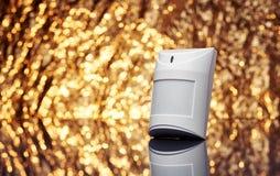 Άσπρος πλαστικός αισθητήρας κινήσεων συναγερμών με το φανταχτερό λαμπρό χρυσό σύνολο υποβάθρου των σπινθήρων από την εστίαση Στοκ Εικόνες