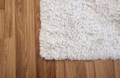 Άσπρος τάπητας κινηματογραφήσεων σε πρώτο πλάνο στο φυλλόμορφο ξύλινο πάτωμα στο καθιστικό, εσωτερική διακόσμηση στοκ εικόνες με δικαίωμα ελεύθερης χρήσης