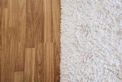 Άσπρος τάπητας πολυτέλειας κινηματογραφήσεων σε πρώτο πλάνο στο φυλλόμορφο ξύλινο πάτωμα στο καθιστικό, εσωτερική διακόσμηση Στοκ Εικόνα