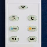 Άσπρος τηλεχειρισμός με τα κουμπιά στο μπλε υπόβαθρο στοκ φωτογραφίες