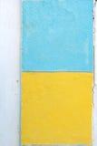 Άσπρος τοίχος με τα κίτρινα και μπλε τετράγωνα χρωμάτων Στοκ φωτογραφία με δικαίωμα ελεύθερης χρήσης