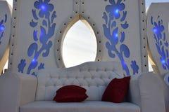 Άσπρος τοίχος με τα μπλε λουλούδια, καναπέ και δύο κόκκινα μαξιλάρια για ένα γαμήλιο βράδυ Στοκ εικόνες με δικαίωμα ελεύθερης χρήσης