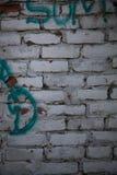 Άσπρος τουβλότοιχος με τα γκράφιτι Στοκ Εικόνα
