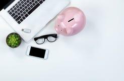 Άσπρος υπολογιστής γραφείου με τη piggy τράπεζα για την έννοια χρηματοδότησης Στοκ Εικόνες