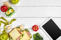 Άσπρος υπολογιστής ταμπλετών με μια κενή οθόνη στον πίνακα κουζινών με τα σάντουιτς, φρέσκα λαχανικά, μπουκάλι νερό και Στοκ Εικόνα