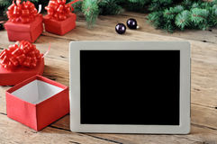Άσπρος υπολογιστής ταμπλετών με τα ανοικτά δώρα Χριστουγέννων στον ξύλινο πίνακα Στοκ εικόνα με δικαίωμα ελεύθερης χρήσης