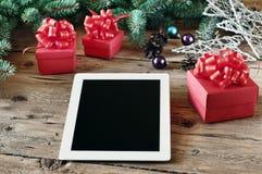 Άσπρος υπολογιστής ταμπλετών με τα δώρα Χριστουγέννων στον ξύλινο πίνακα στενό Στοκ φωτογραφία με δικαίωμα ελεύθερης χρήσης