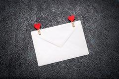 Άσπρος φάκελος με τους γόμφους ενδυμάτων με τις καρδιές Στοκ Φωτογραφίες
