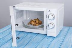 Άσπρος φούρνος μικροκυμάτων, σε μια μπλε ξύλινη επιφάνεια για τη θέρμανση των τροφίμων στοκ φωτογραφίες με δικαίωμα ελεύθερης χρήσης