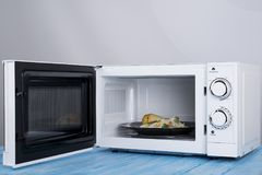 Άσπρος φούρνος μικροκυμάτων, σε μια μπλε ξύλινη επιφάνεια για τη θέρμανση των τροφίμων Στοκ εικόνες με δικαίωμα ελεύθερης χρήσης