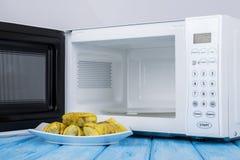 Άσπρος φούρνος μικροκυμάτων, σε μια μπλε ξύλινη επιφάνεια για τη θέρμανση των τροφίμων Στοκ Φωτογραφία