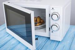 Άσπρος φούρνος μικροκυμάτων, σε μια μπλε ξύλινη επιφάνεια για τη θέρμανση των τροφίμων Στοκ Εικόνα