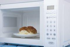 Άσπρος φούρνος μικροκυμάτων, σε μια μπλε ξύλινη επιφάνεια για τη θέρμανση των τροφίμων Στοκ Φωτογραφίες