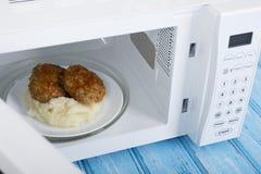 Άσπρος φούρνος μικροκυμάτων, σε μια μπλε ξύλινη επιφάνεια για τη θέρμανση των τροφίμων Στοκ φωτογραφία με δικαίωμα ελεύθερης χρήσης