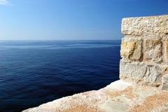 Άσπρος φράκτης τούβλου και μπλε ωκεανός στοκ εικόνες
