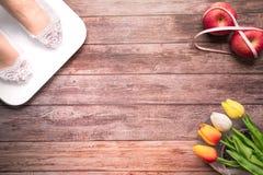 Άσπρος ψηφιακός κλίμακας βάρους με τα πόδια γυναικών που στέκονται στο κόκκινο μήλο κλίμακας και διατροφής δεσμεύει με τη μέτρηση Στοκ Φωτογραφία