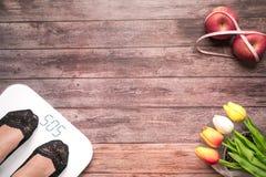 Άσπρος ψηφιακός κλίμακας βάρους με τα πόδια γυναικών που στέκονται στο κόκκινο μήλο κλίμακας και διατροφής δεσμεύει με τη μέτρηση Στοκ Εικόνες