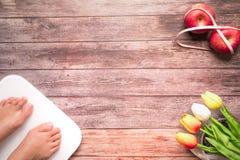 Άσπρος ψηφιακός κλίμακας βάρους με τα πόδια γυναικών που στέκονται στο κόκκινο μήλο κλίμακας και διατροφής δεσμεύει με τη μέτρηση Στοκ φωτογραφία με δικαίωμα ελεύθερης χρήσης