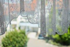 Άσπρος curtian με τις διακοσμήσεις σε ένα παράθυρο Στοκ φωτογραφίες με δικαίωμα ελεύθερης χρήσης