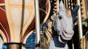Άσπρο άλογο με την κίτρινη σέλα σε έναν Γάλλο εύθυμος-πηγαίνω-γύρω από, ζουμ μέσα φιλμ μικρού μήκους