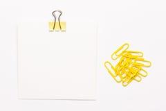 Άσπρο έγγραφο σημειώσεων και κίτρινα paperclips Στοκ Φωτογραφίες