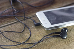 Άσπρο έξυπνο τηλέφωνο με τα ακουστικά Στοκ εικόνα με δικαίωμα ελεύθερης χρήσης