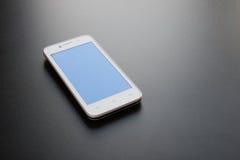 Άσπρο έξυπνο τηλέφωνο με την μπλε οθόνη στο μαύρο πίνακα Στοκ εικόνες με δικαίωμα ελεύθερης χρήσης