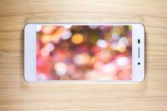 Άσπρο έξυπνο τηλέφωνο με την οθόνη στο ξύλινο υπόβαθρο Στοκ εικόνα με δικαίωμα ελεύθερης χρήσης