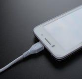 Άσπρο έξυπνο τηλέφωνο που χρεώνει με το καλώδιο USB στο μαύρο πίνακα Στοκ φωτογραφία με δικαίωμα ελεύθερης χρήσης