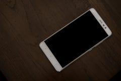 Άσπρο έξυπνο τηλέφωνο στον ξύλινο πίνακα στοκ φωτογραφίες