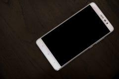 Άσπρο έξυπνο τηλέφωνο στον ξύλινο πίνακα στοκ εικόνα με δικαίωμα ελεύθερης χρήσης