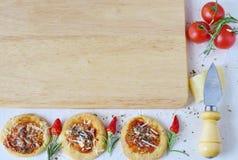 Άσπρο αγροτικό υπόβαθρο με τον ξύλινο τέμνοντα πίνακα, σπιτικό μπισκότο σε μια μορφή πίτσας με το τσίλι, δεντρολίβανο, κεράσι Στοκ φωτογραφία με δικαίωμα ελεύθερης χρήσης