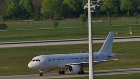 Άσπρο αεροπλάνο που κάνει το ταξί στον αερολιμένα του Μόναχου, πράσινη χλόη απόθεμα βίντεο